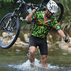 Mountain biker wading through a river, Borneo