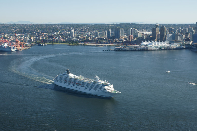 Cruise ship leaves Vancouver and Canada Place as seen from the air.