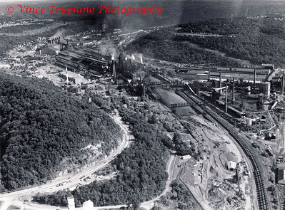 Weirton Steel Company in Weirton, WV - 1983.  Looking south from the north end of Weirton, the massive ore piles, the old Coke Plant on the right, behind is the Tin Mill, on the left are the Blast Furnaces, the old Blooming Mill, the BOP, and farther south is the Strip Steel. On the hill in the far right is William's Country Club.