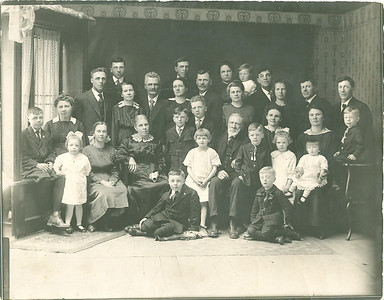 Mom near front right with bow in her hair. Grandma behind her right shoulder. Grandpa behind grandma's left shoulder. Around 1920.