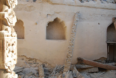 Debris inside one of the houses in Al Munisifeh.  The arched recesses were used for storage, the wooden pegs in the wall were used to hang lamps for light.