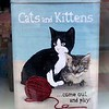 A tin with two cats and a ball of wool and the slogan cats and kittens come out and play in a shop  in Albury, NSW in October 2017