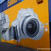 Mural of a Nikon DSLR camera and a roll of film on the wall outside the Camera House store in Albury, NSW in October 2017