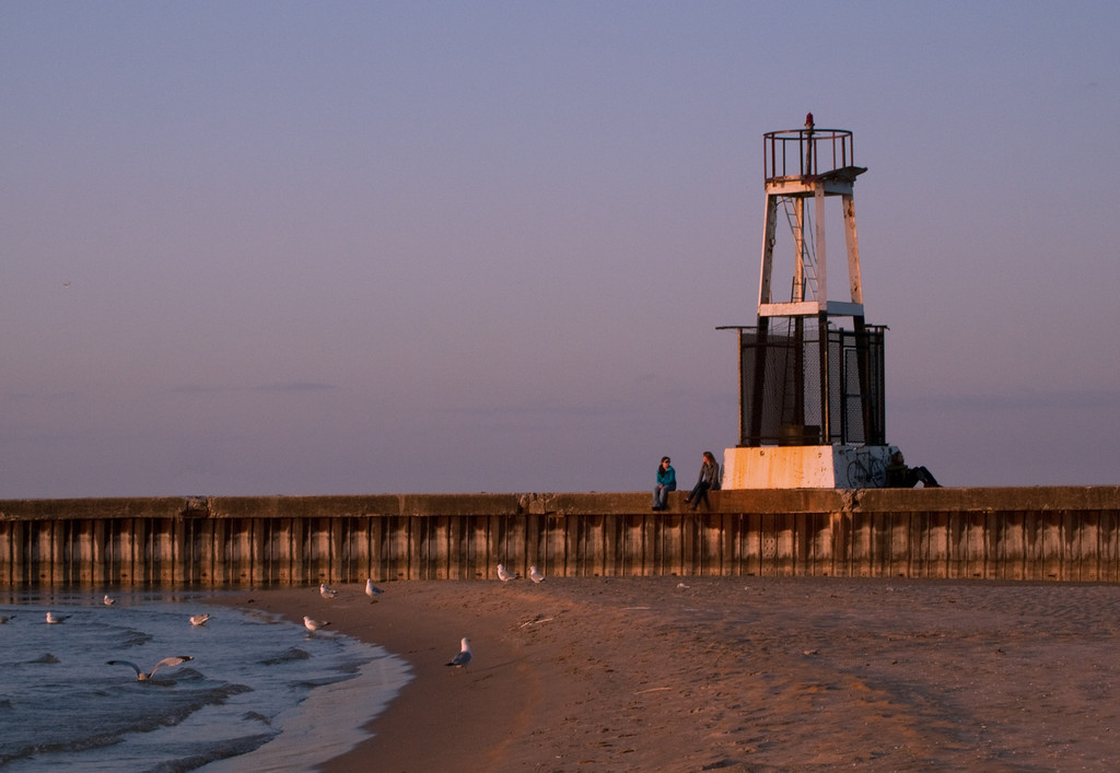 Two girls and a guy rest up against the lighthouse to watch the sunset.