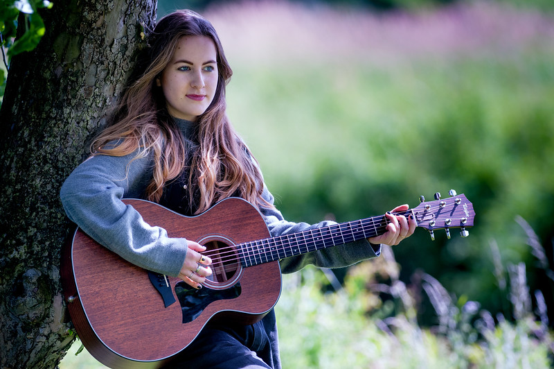 19 year old Charlotte Foley plays her guitar and practices some of the songs she has written about her experiences of dementia and being a carer, in the garden of her home in Downton, Wiltshire. 5th July, 2016 - Picture Andy Brooks