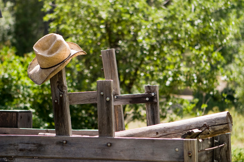 A straw cowboy hat hanging from a post on an old wood wagon.