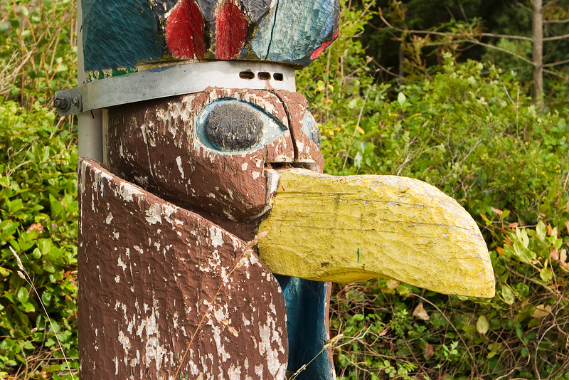 Detailed view of a bird carving on the base of a totem pole at a boy scout camp. The paint is peeling from weathering and age.
