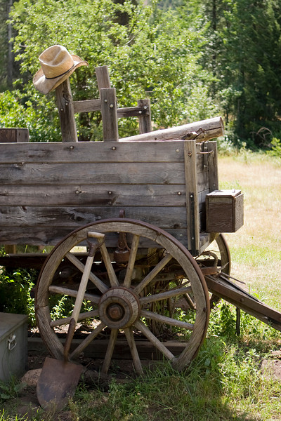 An old wagon from the American West with a straw cowboy hat on one of the wood support posts.