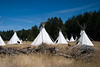 A small Native American village located at the edge of a forest. This group of teepees in the wilderness are used for summer camping.
