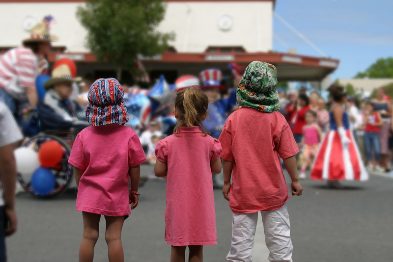 Three children, dressed in identical red shirts, watching the 4th of July parade in a small town in the San Juan Islands. Independence Day is a great occasion to bring out the red, white and blue as some of the street costumes show.