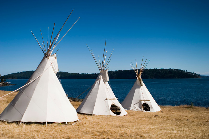 Three teepees are lined up in a row in front of water. These teepees are used to provide shelter at a summer camp. Teepees were one form of traditional shelter used by native americans.