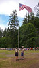Three boy scouts raising the American flag during the daily flag ceremony at Boy Scout summer camp. Several local troops in the background are watching.