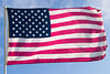 The American flag, flying in a strong wind, is almost perfectly horizontal. Every stripe and every star is visible.