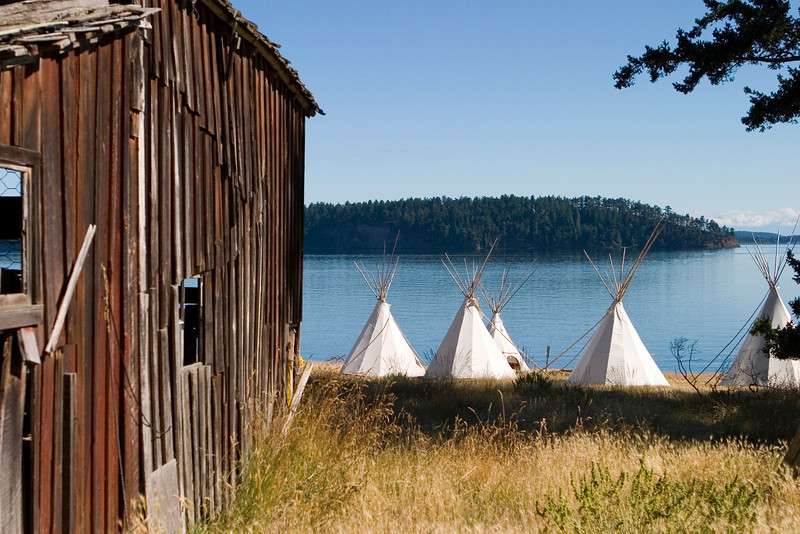 A group of teepees located near an old barn. This scene represents the mix of the American West with the traditional Native American cultures.