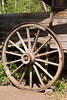 An old, weathered wagon wheel in the American West is an example of the rustic charm of the country. This wheel is covered with an iron strip for durability.