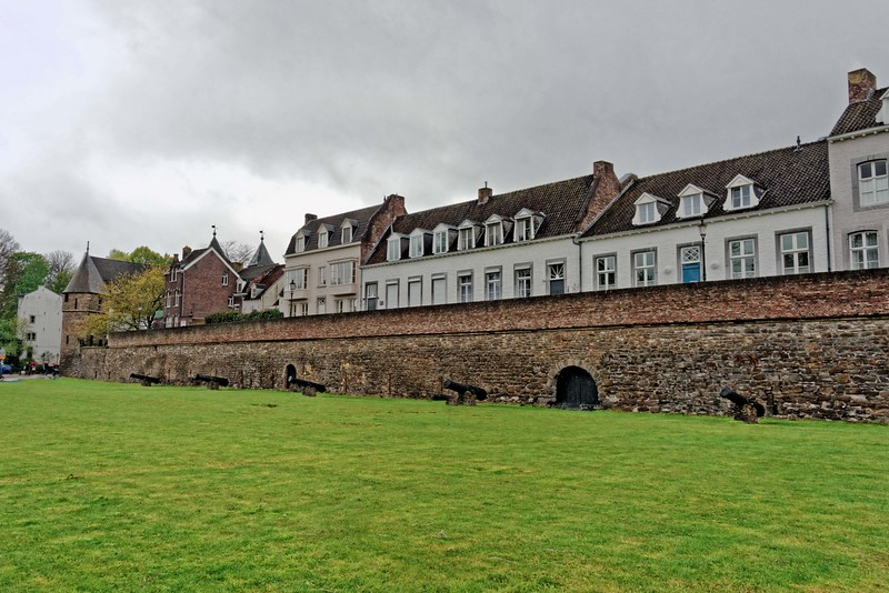 Houses behind a medieval city wall, with canons in the foreground.