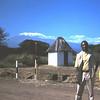 Met onze chauffeur bij de ingang van het Amboseli NP. Op de achtergrond de Kibo, de hoofdtop van de Kilimanjaro.