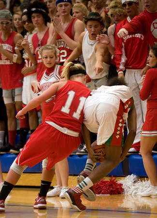 Connersville's Taylor Stephen and Anderson's Dabriona Williams fight for a loose ball in front of the Connersville student cheering section as they try to assist the officials make the call. Anderson fell to Connersville in the final of sectional #9 at Greenfield-Central Saturday, February 9, 2013. Photo by Richard Sitler