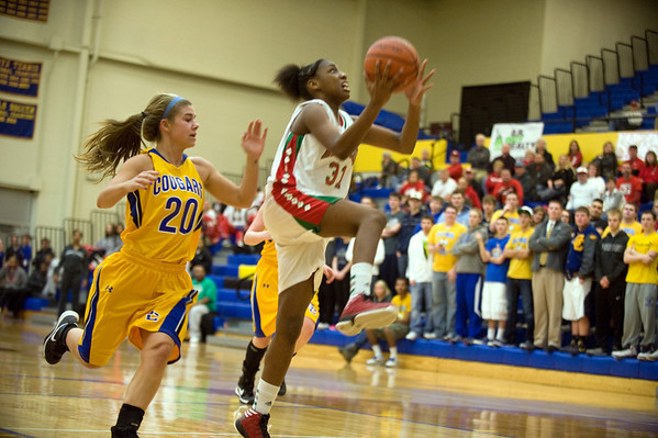 Anderson's Dabriona Williams finishes a fast break as she scores ahead of defender Greenfield-Central's Brooke Bell. Anderson High School faces Greenfield-Central High School in the first round of girl's basketball sectional #9 at Greenfield-Central High School Monday, February 5, 2013. Photo by Richard Sitler