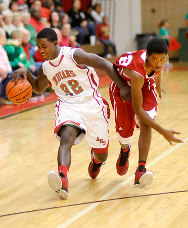 Anderson's Jerian Beard brings the ball down court as he is guarded by Manual's DeJaun Johnson on Saturday.
