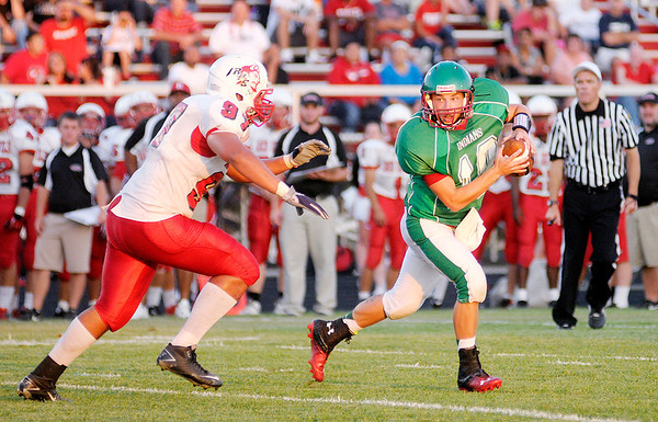Don Knight/The Herald Bulletin<br /> Anderson quarterback Gaven Owens rolls out of the pocket under pressure from Richmond's Anthony Officer as the Indians hosted the Red Devils on Friday.