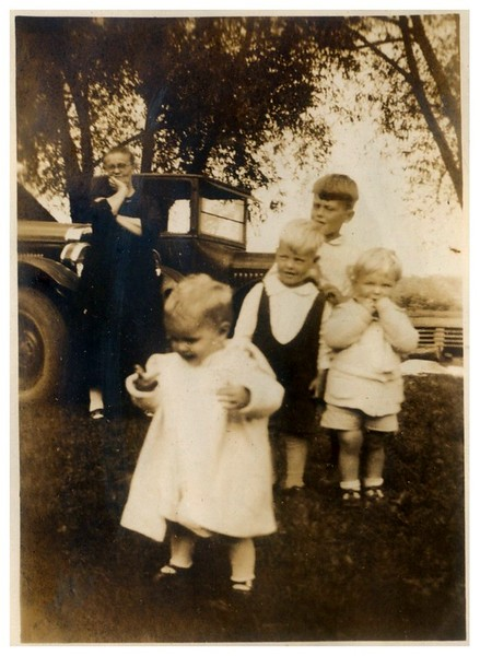 Marie Fredine standing by car.<br /> <br /> Who are the children?<br /> <br /> Laurie thinks that Jeanne, Spencer and Stan are not in this photo.<br /> <br /> Dave wonders if maybe the 3 older children are Jeanne, Spencer, and Stan?<br /> <br /> This photo was with a group of Fredine photos, so these are maybe Fredine cousins of Jeanne's.