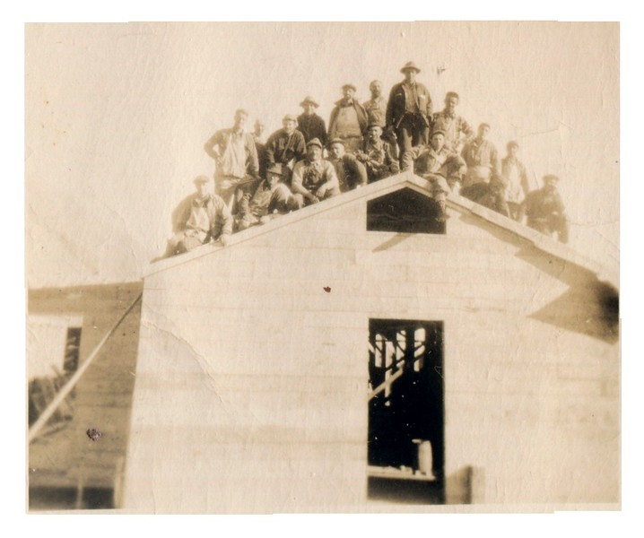 """Written on back of original photo:  """"Fred in Alaska""""<br /> <br /> Which one is Fred? My guess, sitting on the left side of the roof, third sitting man from the left."""
