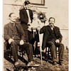 Gary confirms that the man standing is Fred Anderson, the child is Stan, the man sitting at the left side of the photo is Fred's father Andrew Anderson, and, the man sitting at the right side of the photo is Fred's grandfather.
