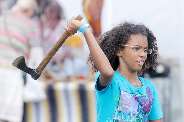 """Don Knight/The Herald Bulletin<br /> Hannah Bowen, 9, throws a tomahawk after receiving some instruction from """"Hawk Man"""" Steve Witt during the Andersontown Powwow on Saturday."""