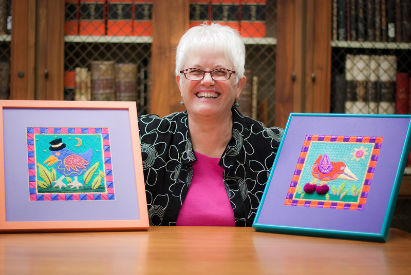 "2011-07-22 Here is my librarian friend Janet posing with two of her most colorful cross-stitch creations. They were on display today at her retirement party, which was quite the shindig. She was kind enough not only to pose, but to give a great smile too! I edited a bit in Lightroom, mostly to correct color issues caused by the all-fluorescent lighting. I love this room with all the old books - they provide such a <a href=""http://www.jawsnap.net/Daily/year4/16022532_dVzfk#1383101170_Dmb7W7G"">great backdrop</a>.  <a href=""http://www.jawsnap.net/Daily/year3/11272102_ACXDJ#944328977_zAJaD"">[last year]</a>"