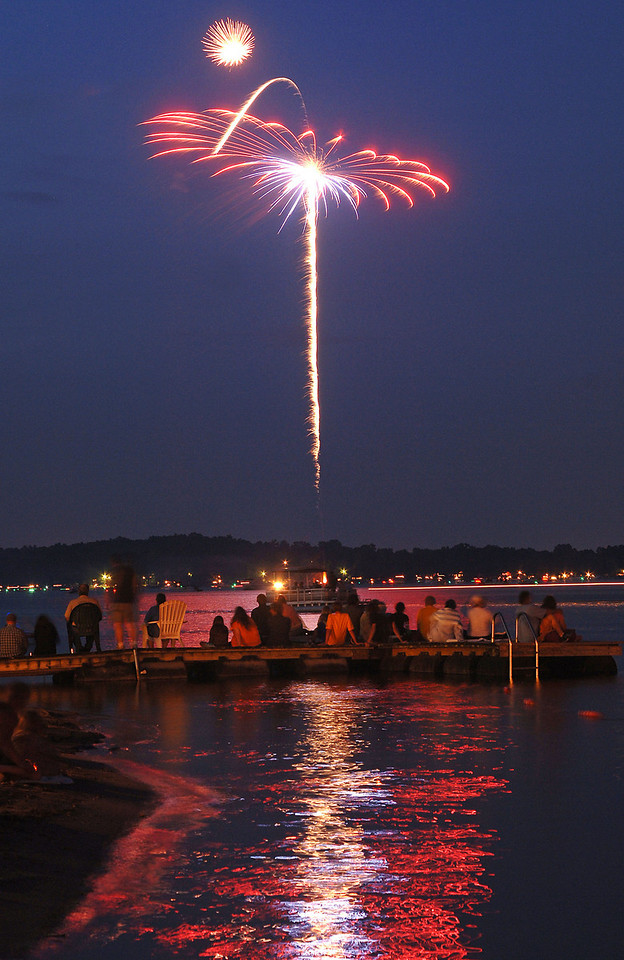 People enjoy the fireworks display from a dock on Whitmore Lake on July 3, 2007.  (Photo by Mark Bialek)