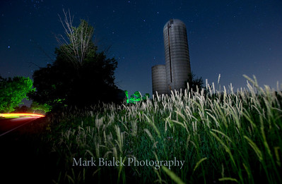A wheat field and silo are illuminated by a passing car's headlights on a clear night just West of Whitmore Lake, Michigan on June 28, 2011.