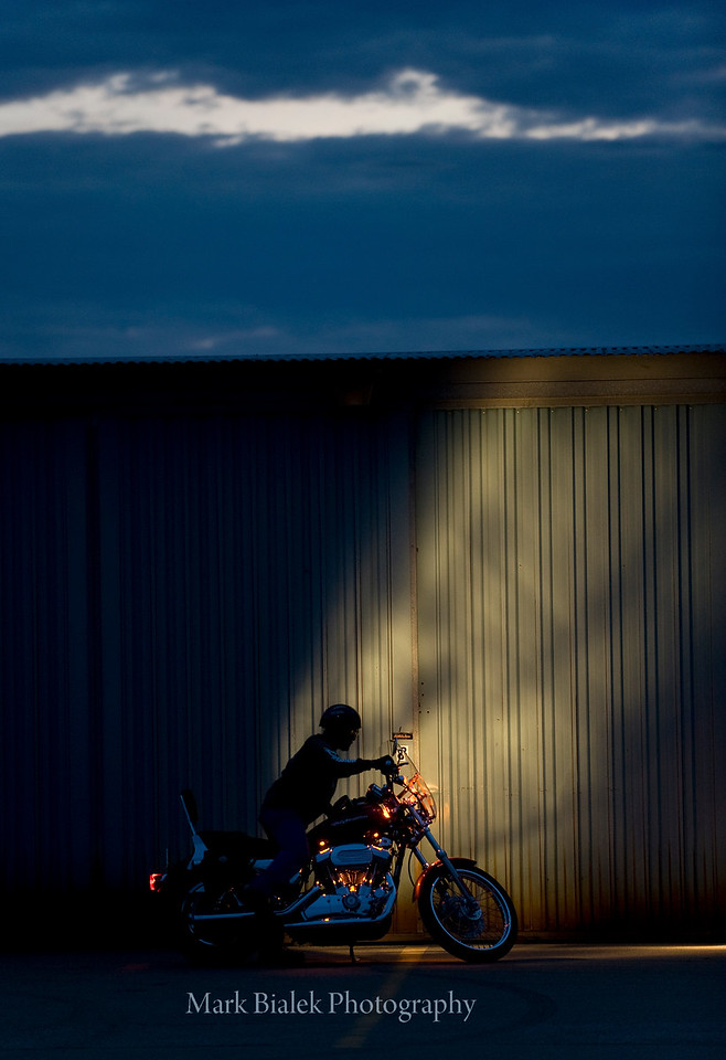 Joe gets on his bike to leave his hanger at dusk at the Ann Arbor Municipal airport on June 10, 2010.  (Photo by Mark Bialek)