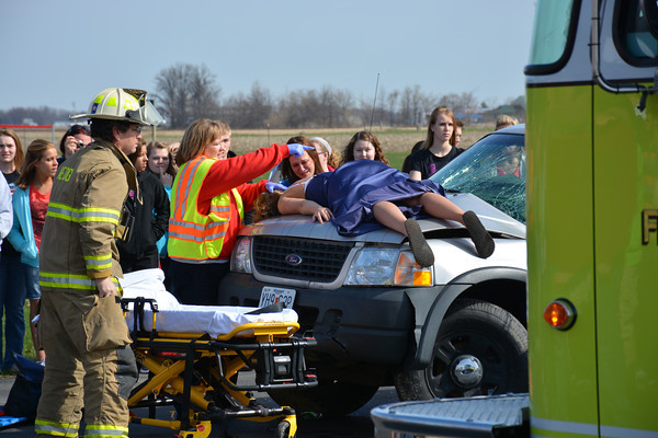 Firefighters prepare to remove Casi Blazich from the scene at the mock crash.