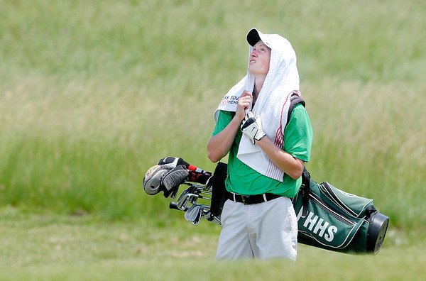 Rylan Denney drapes a towel over his head trying to get some relief from the heat and humidity.