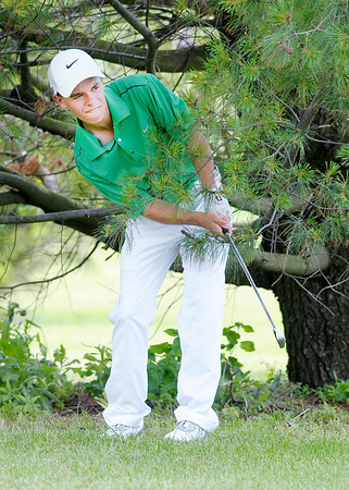 Zach Farrer hits back to the fairway after his tee shot on the 8th hole landed near a pine tree.