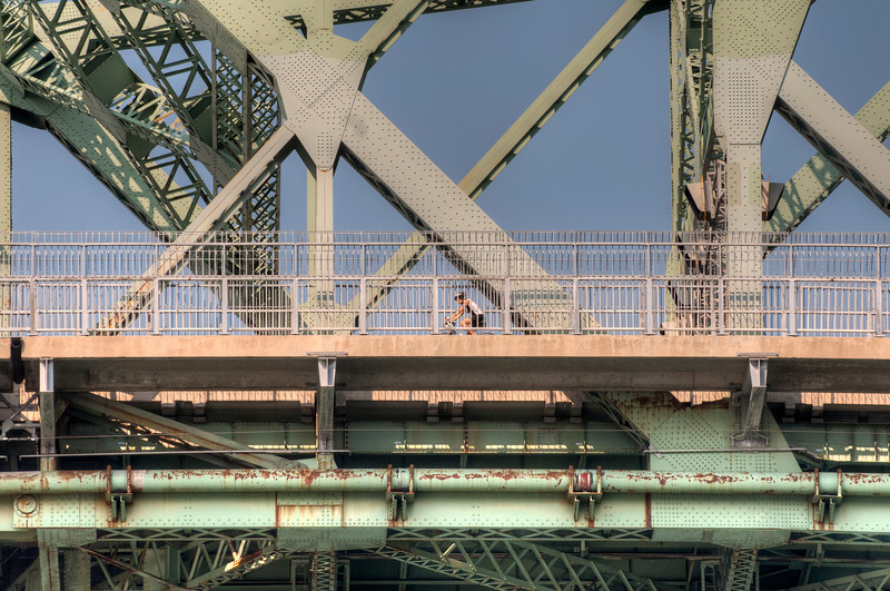Cyclist on the 1930 Jacques Cartier bridge, Montreal, Quebec, Canada.