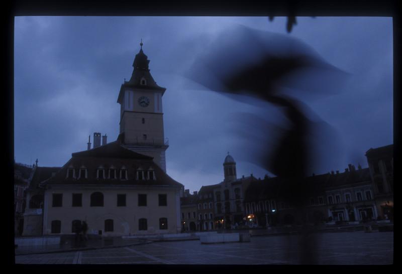 Man with umbrella, city square, Brasov, Romania.