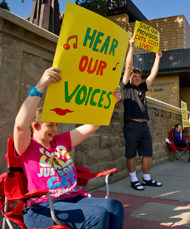 Easter Seals clients Rebecca Cichonski, left, and Dan French wave signs during a demonstration in front of the Sheridan County Courthouse on Thursday. The demonstration was to bring awareness to proposed changes in state funding for programs that provide services for adults and children with developmental disabilities. (Justin Sheely/The Sheridan Press)