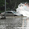 A sedan drives through the flooded intersection at Badger and Loucks Street Tuesday evening. The intersection flooded during the thunderstorm after the storm drains were blocked by garbage and debris. Police temporarily closed the intersection until the City Street Division could unblock the drains.