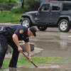 Sheridan Patrol Officer Scott Brastrup uses a shovel to unblock a storm drain at the flooded intersection of Badger and Loucks Street Tuesday evening. The intersection flooded after garbage and debris blocked several drains during Tuesday's deluge.