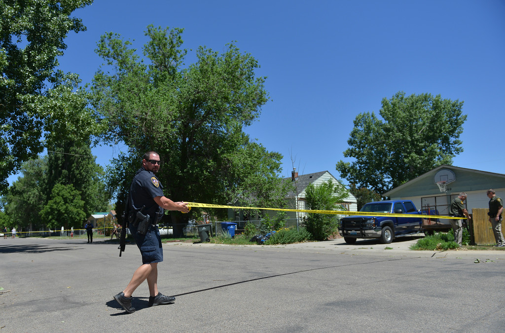 Justin Sheely   The Sheridan Press<br /> A Sheridan Police officer pulls tape across the street near the scene where a man reportedly fired guns in random directions Wednesday afternoon on Spaulding Street. A man was arrested Wednesday after firing multiple guns at his home in north Sheridan. The man, identified as Adam Heldik, presents no threat to the public, Sheridan Police Department Lt. Travis Koltiska said. There is no indication he was attempting to shoot at anyone, although he was firing in random directions from his porch, according to a neighbor who witnessed the event. The home is near the corner of West Ninth Street and Spaulding Street, roughly four blocks from the police department.
