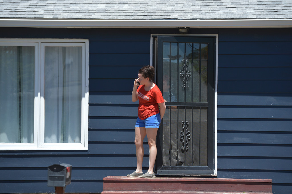 Justin Sheely   The Sheridan Press<br /> A resident looks out from her front door as authorities respond to a shooting nearby Wednesday afternoon on Spaulding Street. A man was arrested Wednesday after firing multiple guns at his home in north Sheridan. The man, identified as Adam Heldik, presents no threat to the public, Sheridan Police Department Lt. Travis Koltiska said. There is no indication he was attempting to shoot at anyone, although he was firing in random directions from his porch, according to a neighbor who witnessed the event. The home is near the corner of West Ninth Street and Spaulding Street, roughly four blocks from the police department.