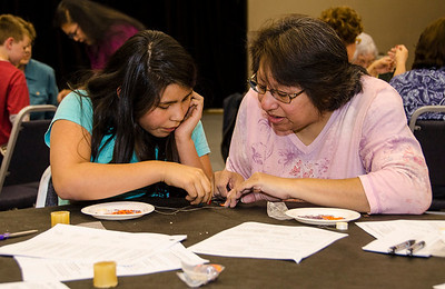 Billie McClure of Ada assists Chasity Boston, 12, of Ardmore at the beading class.