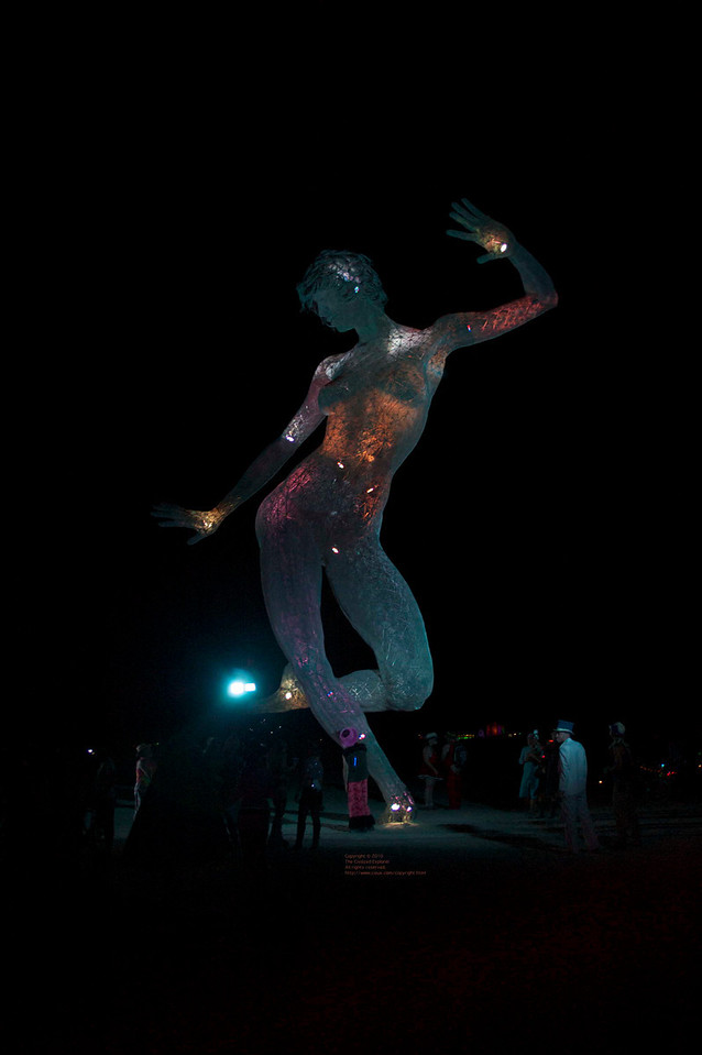 """Bliss Dance, by Marco Cochrane<br /> <a href=""""http://blissdance.org/"""">http://blissdance.org/</a><br /> This was one of the most popular pieces on the playa, and we have lots of photos and video of it. It is supported on one foot, welded to cross pieces which are buried in the playa. See the link to read about its construction. The statue was lighted internally with changing colors."""