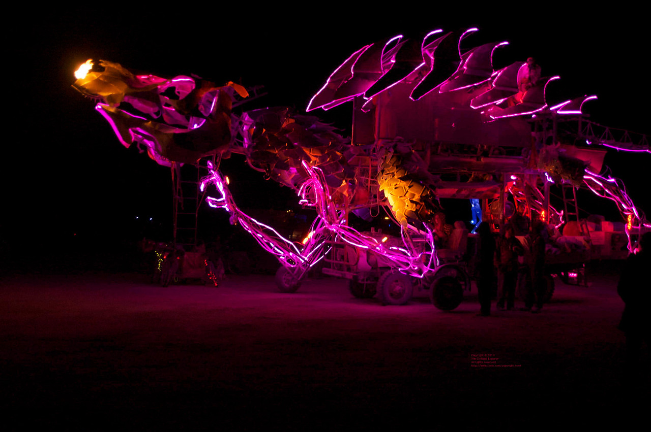 A fire-breathing dragon art car at night on the playa.