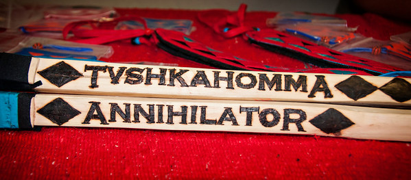 The stickball sticks used by Tvshka Homma team member Joseph Jefferson with wood-burnt text.