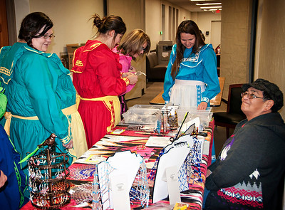Employees dressed in traditional attire browse the selection of art from Martha Dewitt.