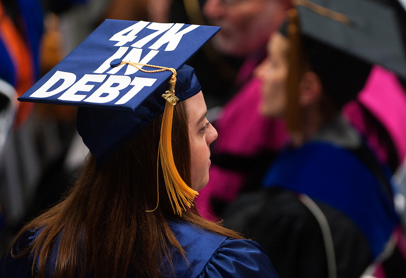 ORONO, MAINE -- 05/09/2015 - A graduate with their debt amount on their hat makes her way to the stage to receive her diploma during the 150th anniversary year graduation at the University of Maine in Orono Saturday. Ashley L. Conti | BDN
