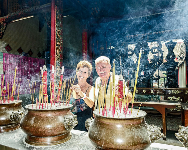 MARIO AND JOAN AT CHINESE TEMPLE, LIGHTING INCENSE.